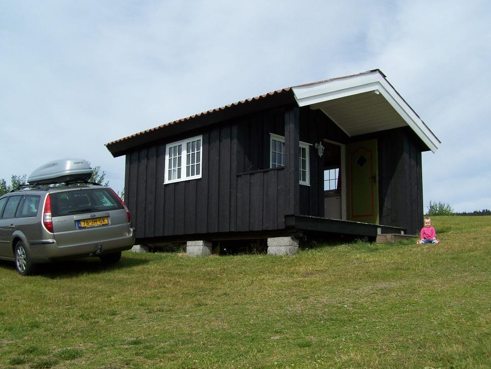 Een ruime kampeerhut, gelegen op een helling aan een meer (Sore Osen, Noorwegen).