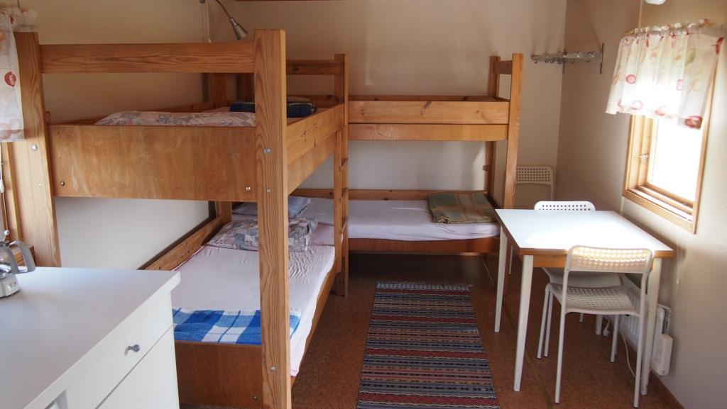De kampeerhutten hebben 2 stapelbedden en een tafeltje met stoelen.