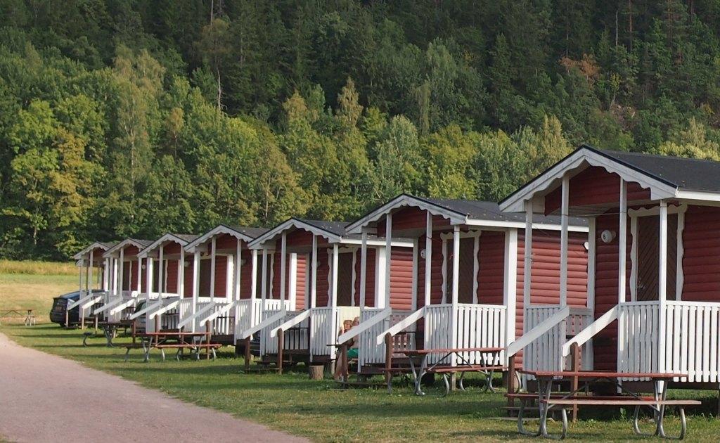 De kampeerhutten op Getingaryds Camping staan op een rijtje aan de zijkant van de camping.