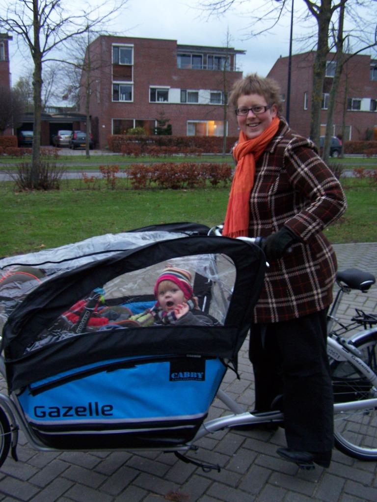 De Gazelle Cabby bakfiets met regenhoes en 1 kind in de Maxi-Cosi en 1 kind op een bankje.