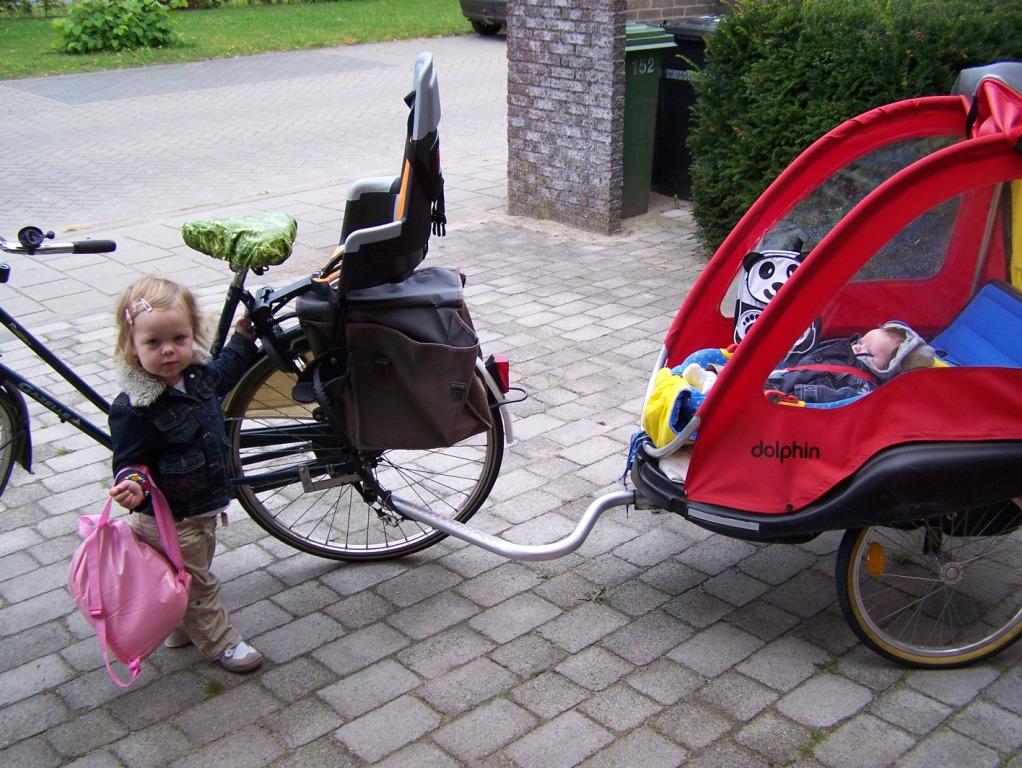 Met een fietskar achter de fiets kan er ook een kind op een kinderzitje op de fiets van de ouder.