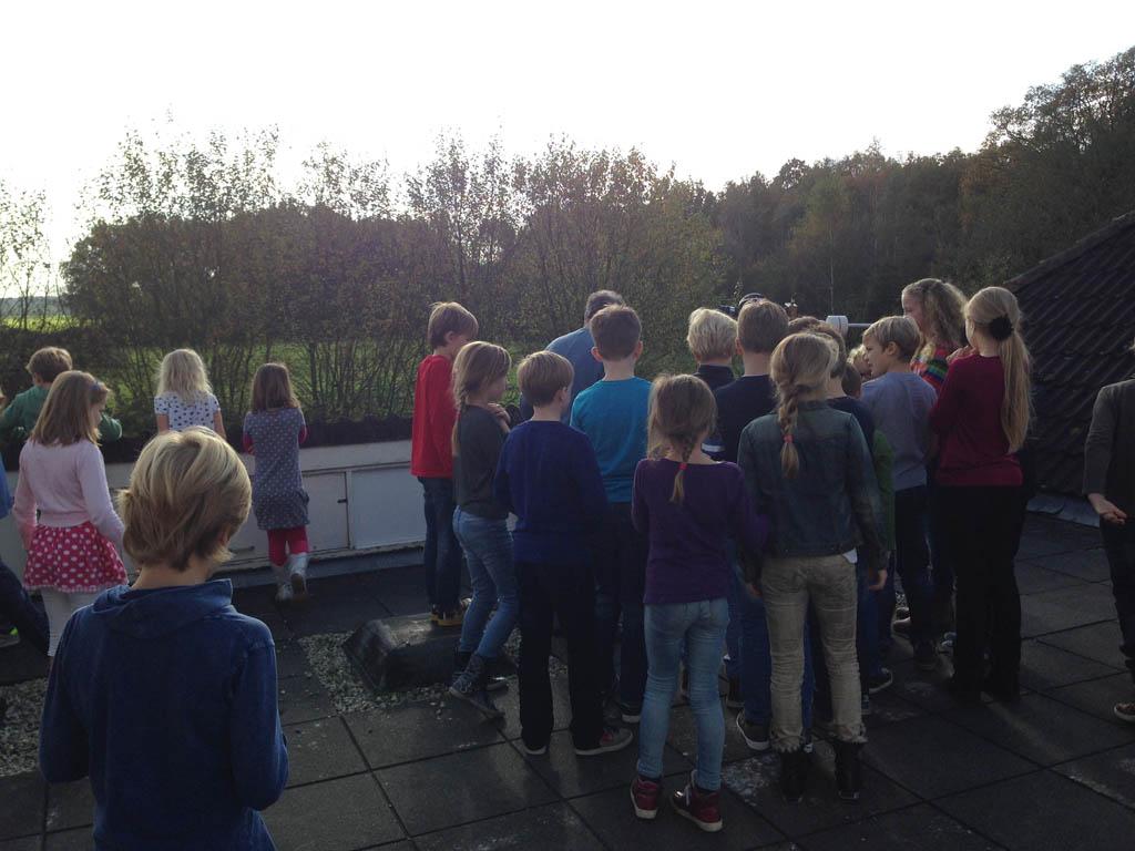 Alle kinderen van Museumjeugduniversiteit staan om de grote telescoop.