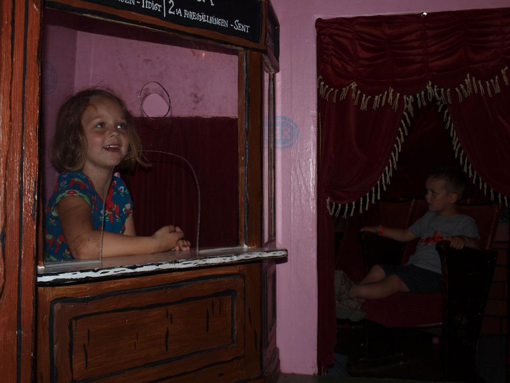 Mini bioscoop: Maureen achter de kassa en Camiel voor het beeldscherm.