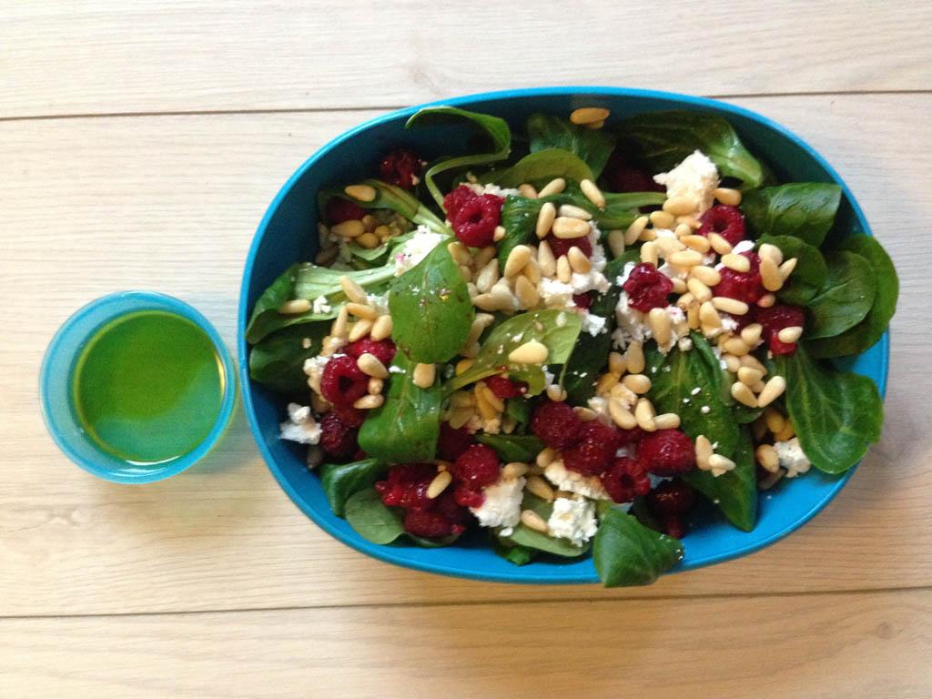 De lunchbox met de salade van veldsla, geitenkaas en framboos. In het kleine bakje zit de dressing.