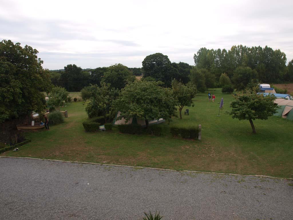 Zicht op de boomgaard met de camping vanuit een van de gites.