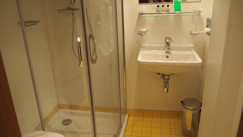 De badkamer met erg mooie gele tegeltjes en eenvoud die past bij de jaren waarin het schip werd opgeleverd.