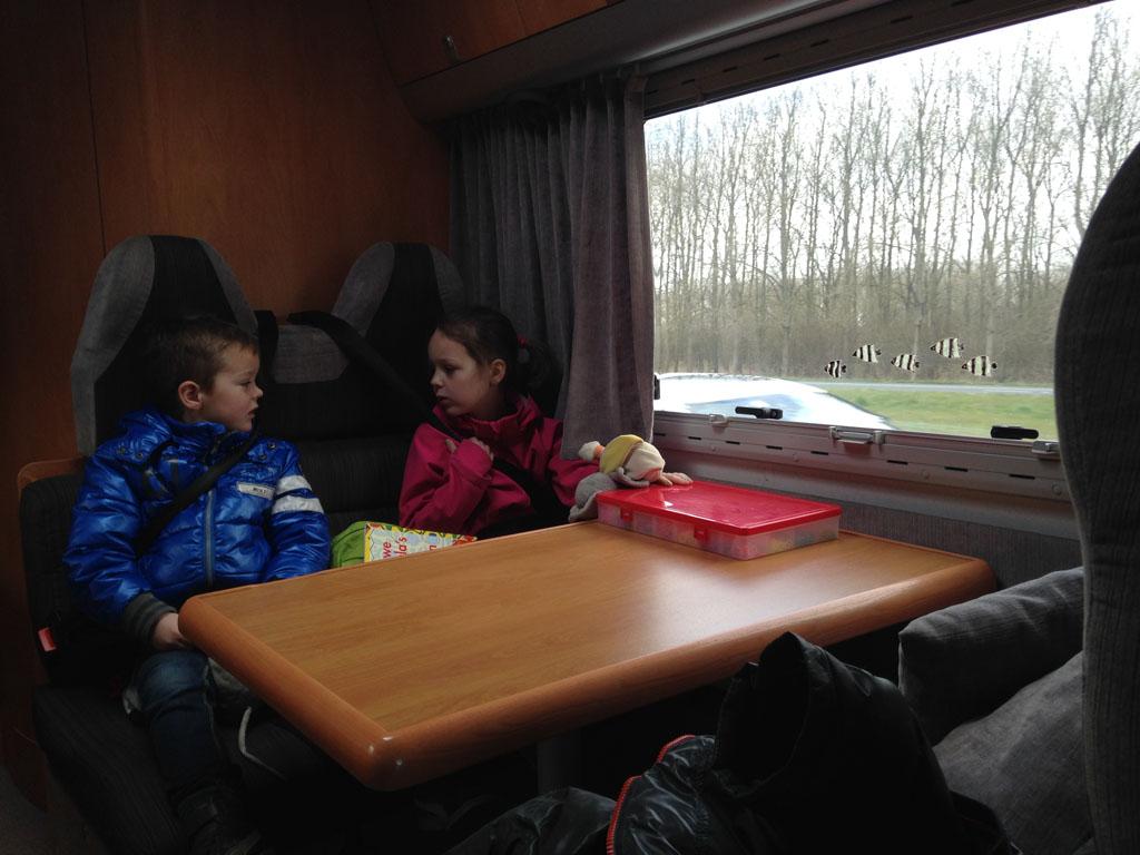 Maureen en Camiel zitten tijdens het rijden in de camper aan tafel.