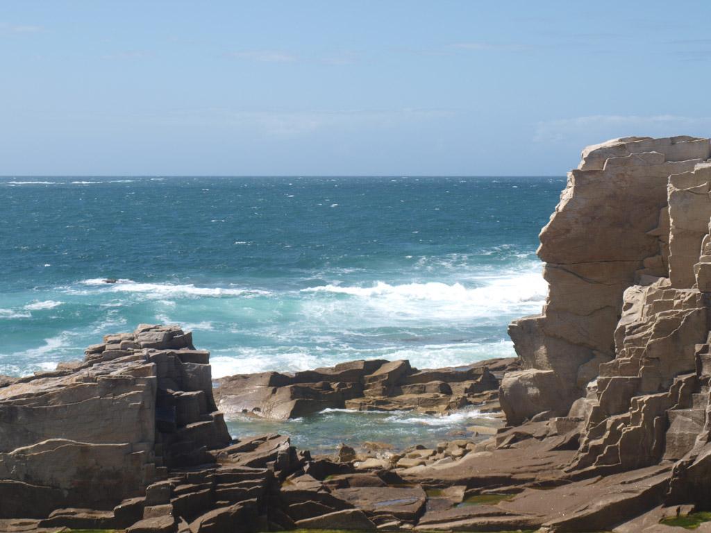 De golven beuken tegen de rotsen.