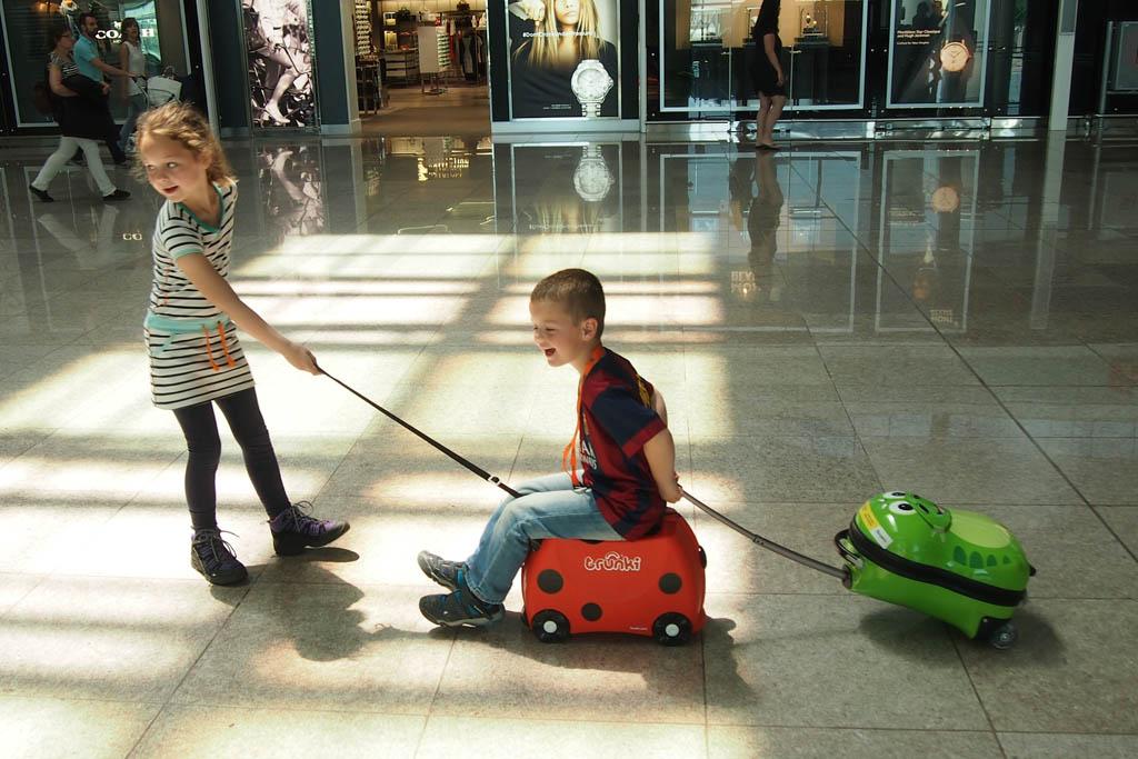 Lol op de luchthaven: Camiel op de Trunki met zijn trolley achter zich. Maureen trok alles makkelijk achter zich aan.