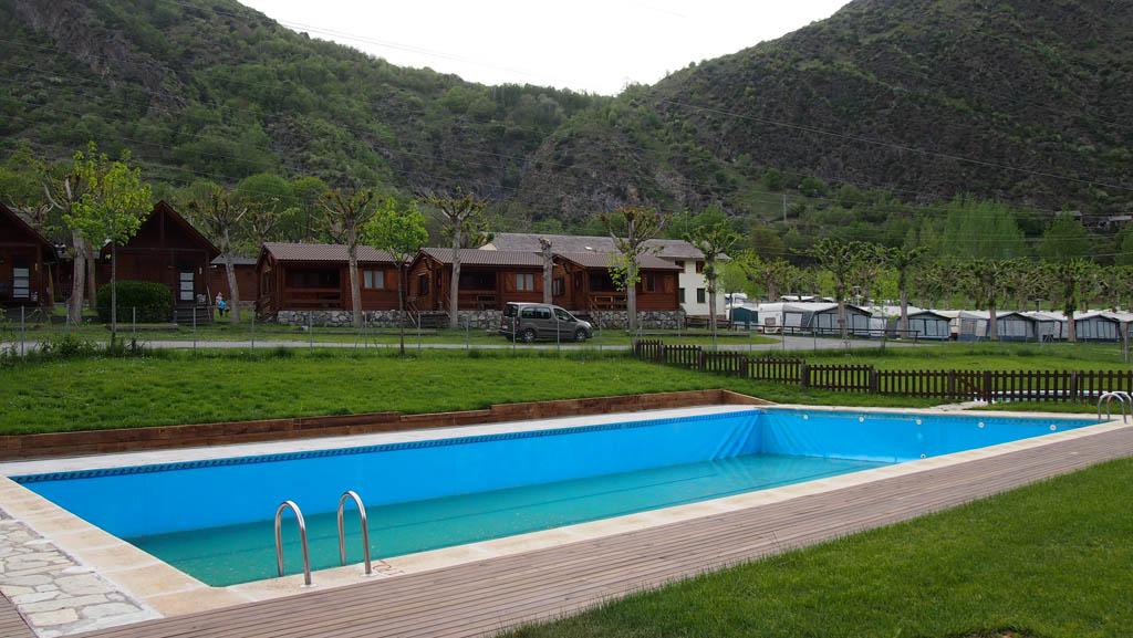 De houten bungalows liggen vlakbij het zwembad.