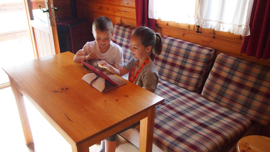 In het woonkamertje staat een tafel met bank en krukjes.
