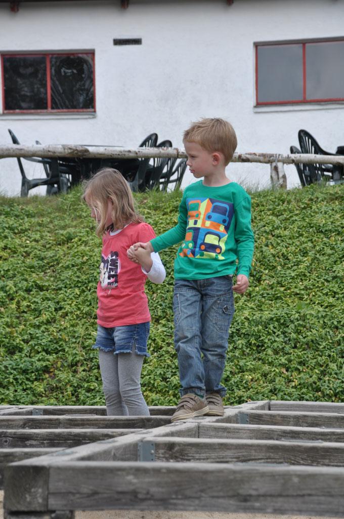 Nynke helpt haar broertje bij het balans-doolhof.