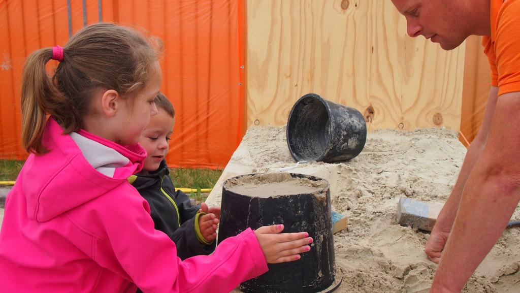 Tegen de zijkant kloppen om de bodemloze emmer los te krijgen van het zand.