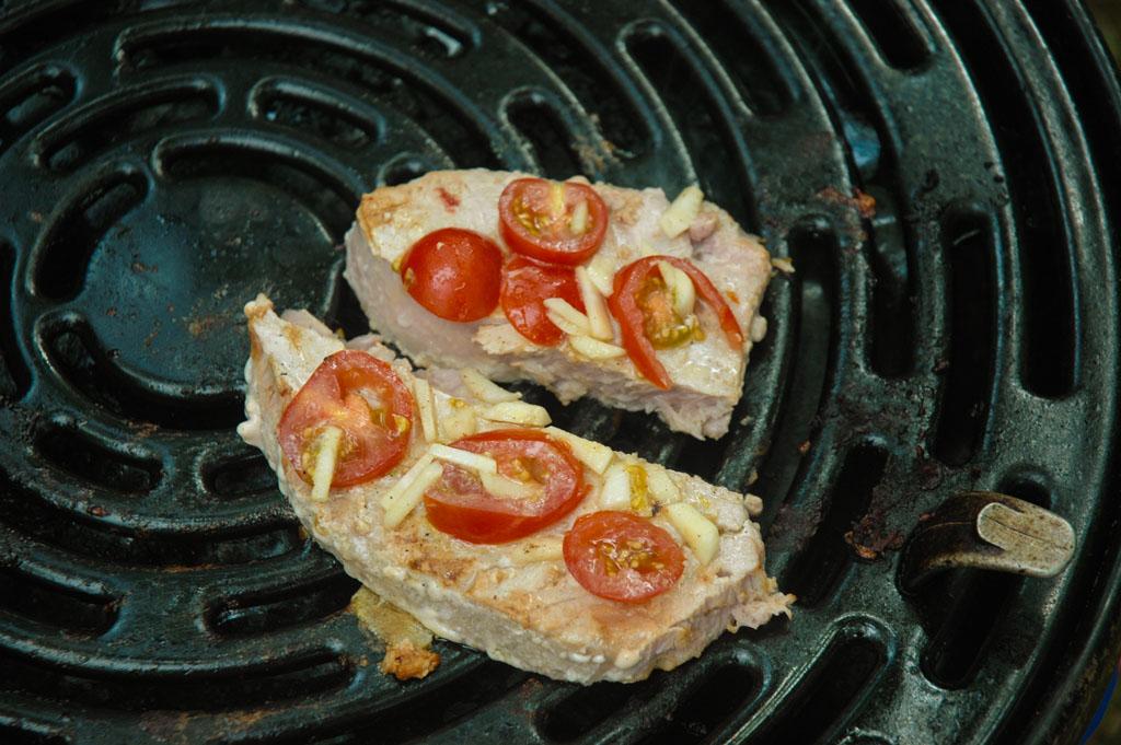 Verse tonijnfilet met tomaat, knoflook en kruiden op de grill van de skottel.