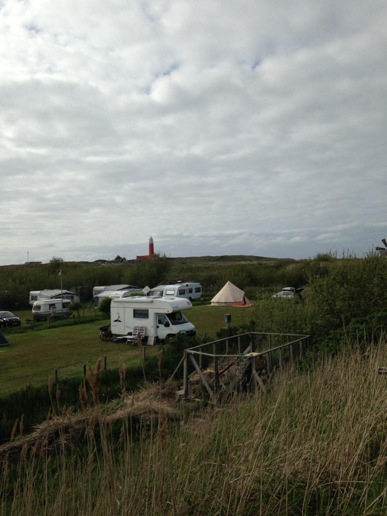 Onze tent tussen de caravans en op de achtergrond de vuurtoren.