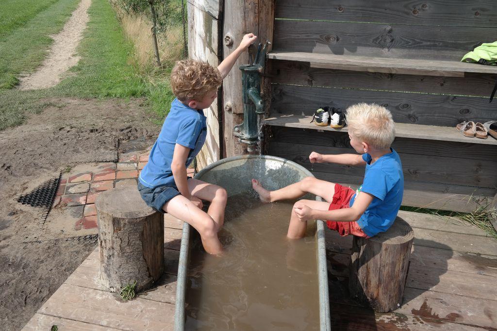 Badkuip met kraan om je voeten te wassen na het blote voetenpad.