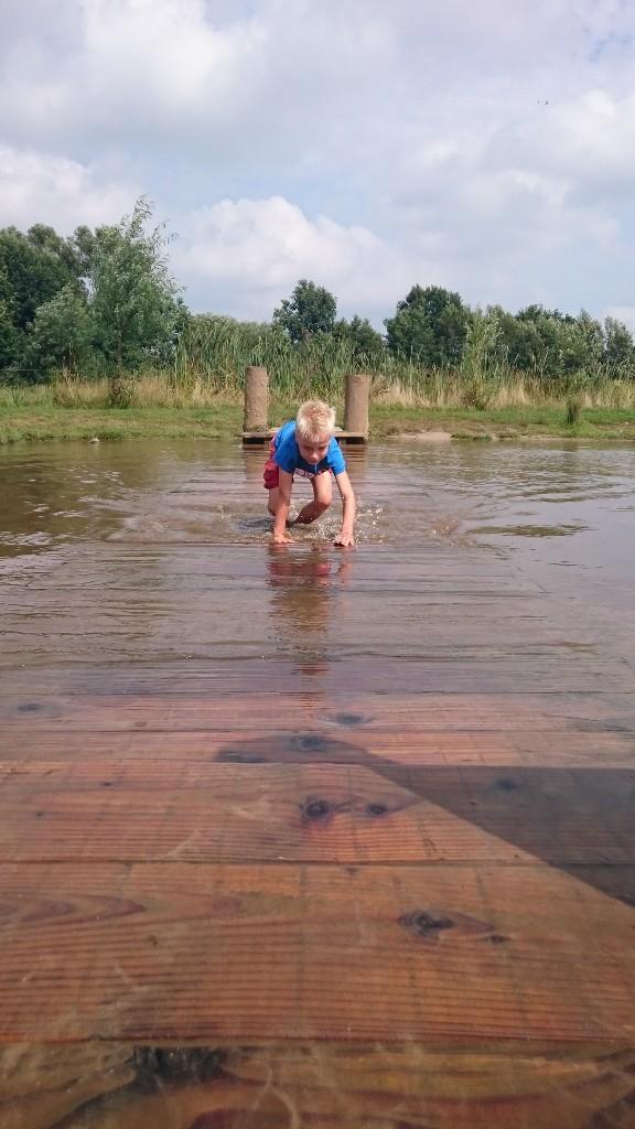 Jesse geniet op de wiebelbrug door het water bij Erve Brooks.