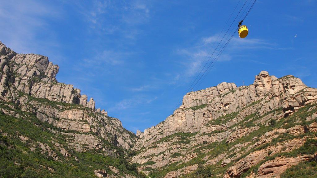 Het kleine gele bakje van de kabelbaan met de stoere berg op de achtergrond.
