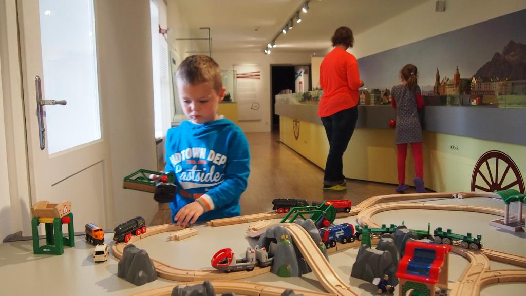 Een miniatuurtreinbaan en houten treintjes om zelf mee te spelen.