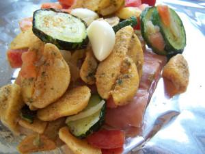 Zalm, aardappeltjes en groente gaan gezamenlijk in de aluminiumfolie.