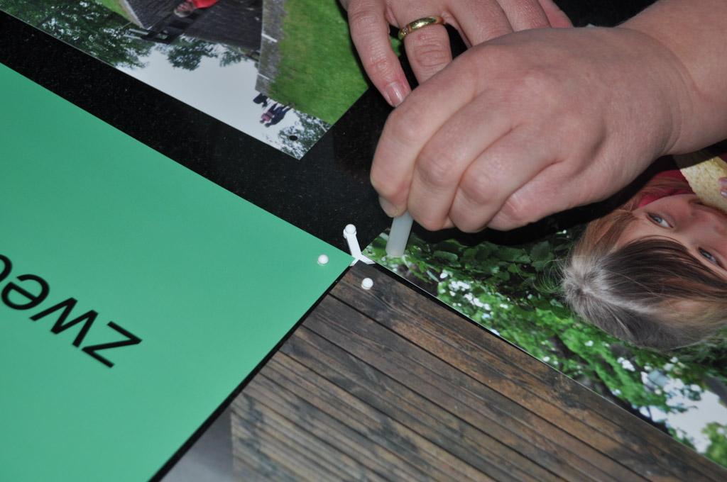 De fotocollage wordt in elkaar gezet met kunststof kruisjes.