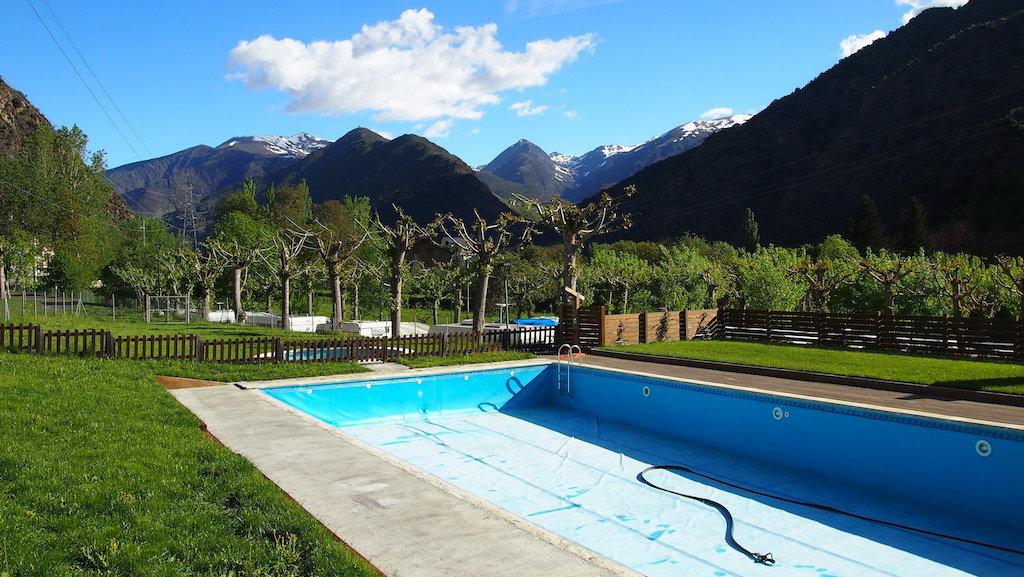 Uitzicht op het zwembad (nog leeg begin mei) en de prachtige bergen.