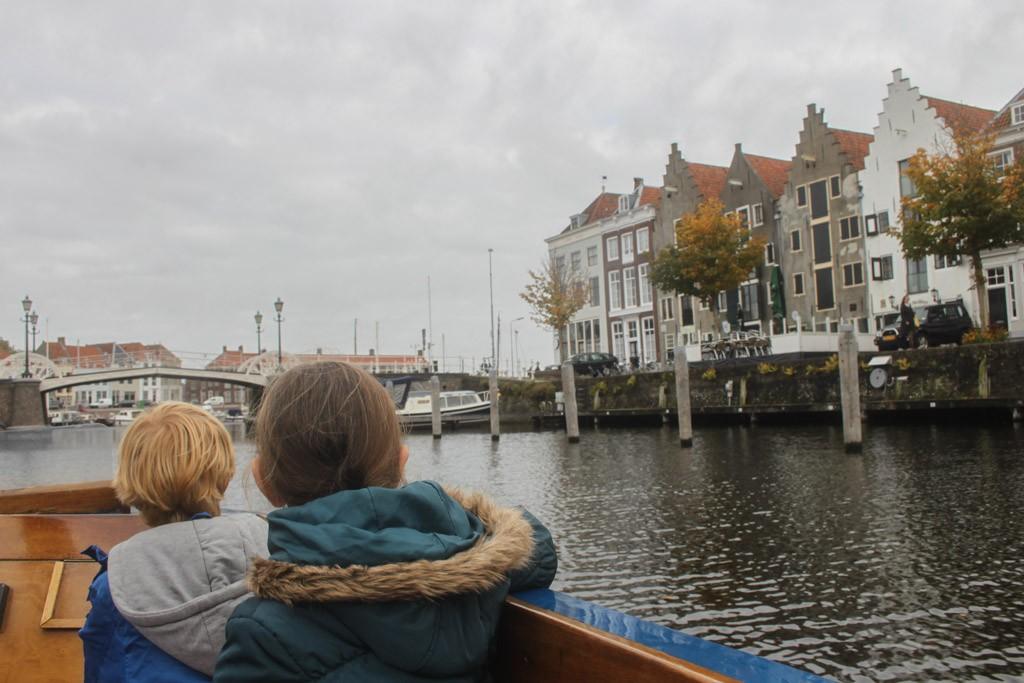 De kinderen luisteren geboeid naar de uitleg over de historische en moderne panden die we vanaf het water zien.