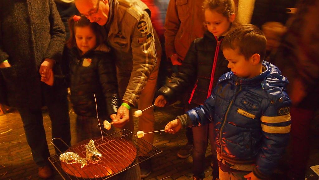 De kinderen rooster marshmallows.