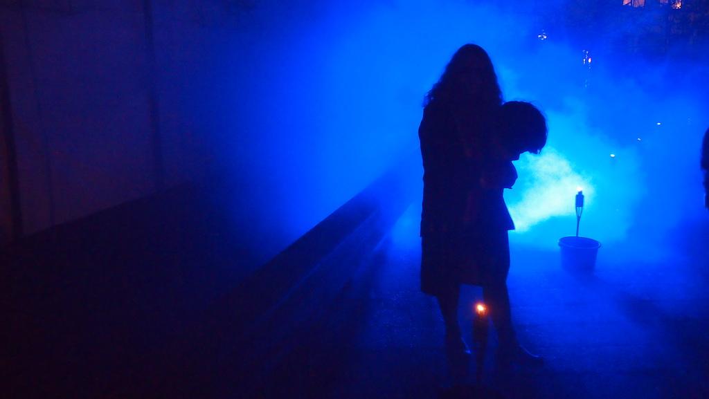 Mystieke sfeer met blauwe mist en spannende figuren.