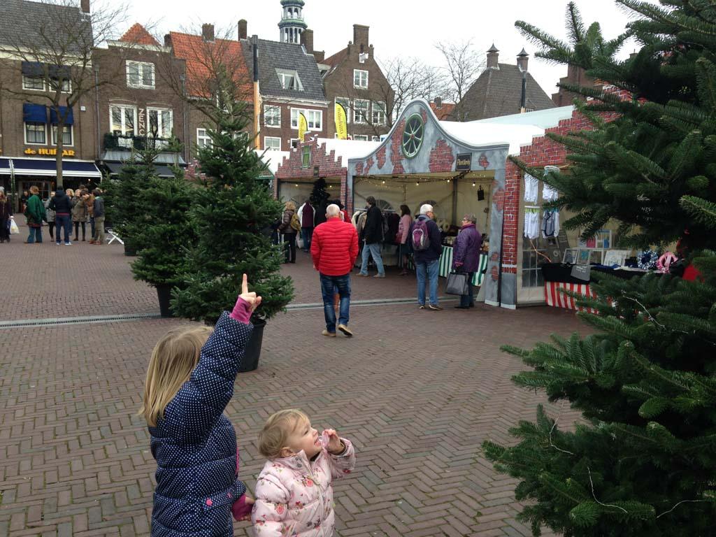 Verstoppen achter de kerstbomen op de markt.