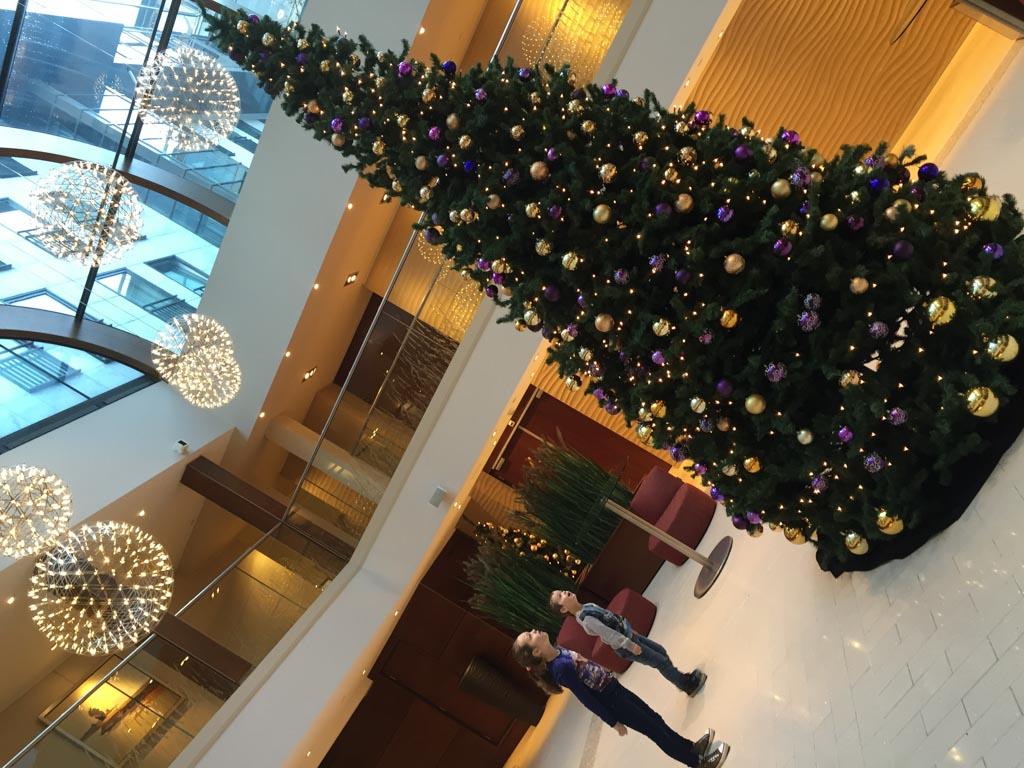 Op weg naar de ontbijtruimte komen we langs een hele grote kerstboom. Maureen en Camiel kijken hun ogen uit.