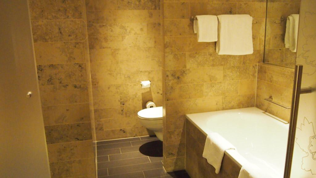 Aan de rechterkant het bad en daarachter het toilet. Links zie je het muurtje van de douche.