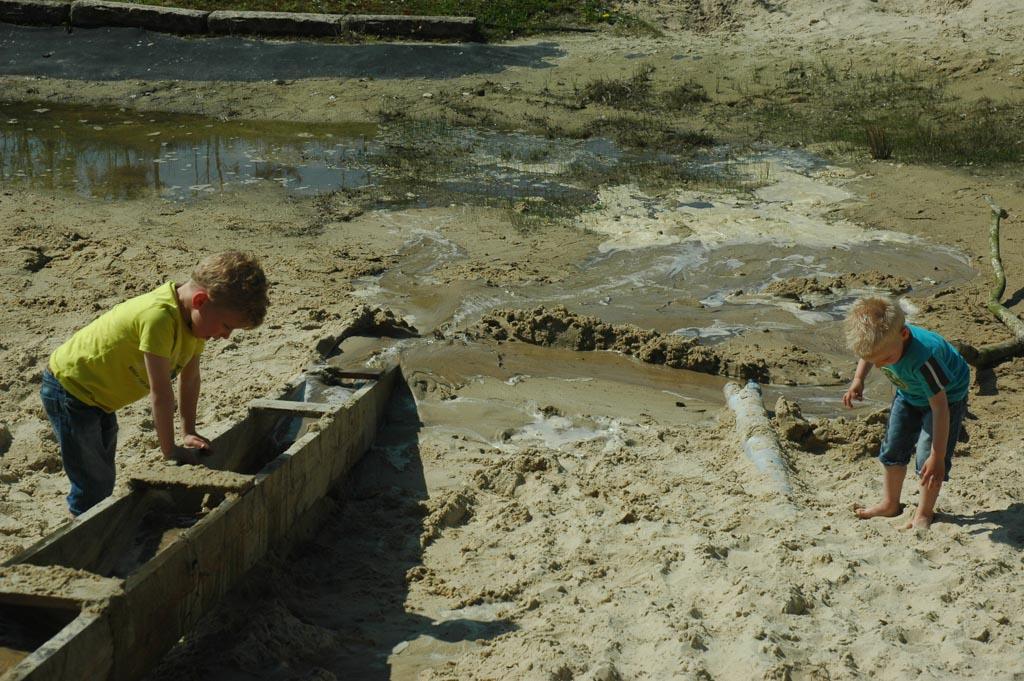 Spelen bij de waterplas met de pomp.