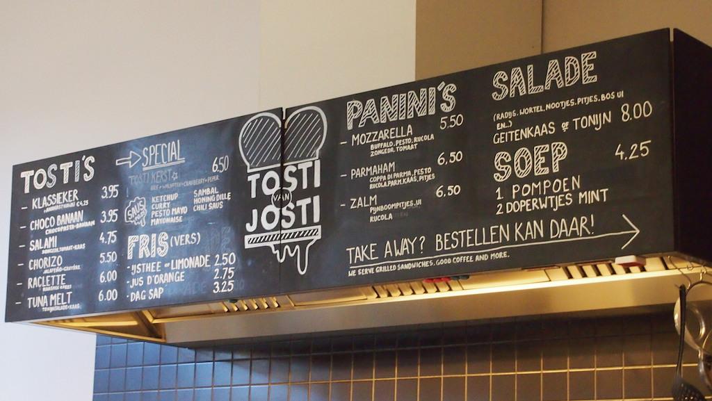 Boven de open keuken hangt de menukaart aan de muur.