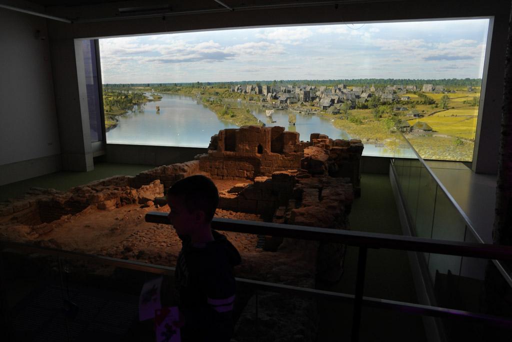 Een ruine met daarachter een impressie van de originele nederzetting.