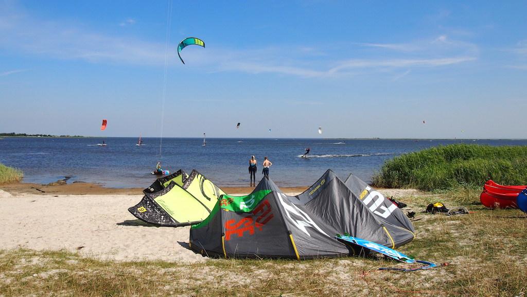 Het strandje ligt vol met kite materiaal.
