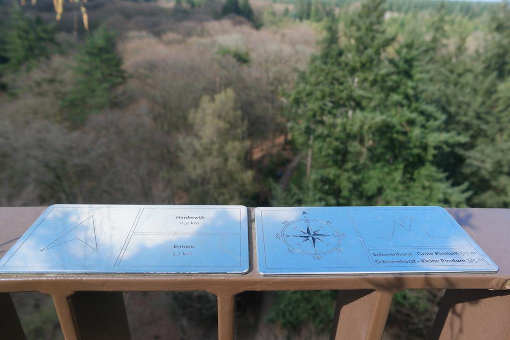 De bordjes op de reling vertellen wat je in het landschap ziet.