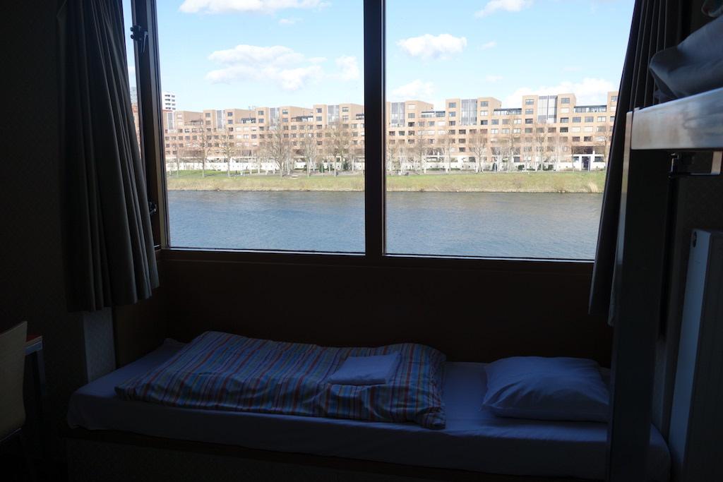 Vanuit onze kamer kijken we uit op de Maas en de wijk Ceramique.