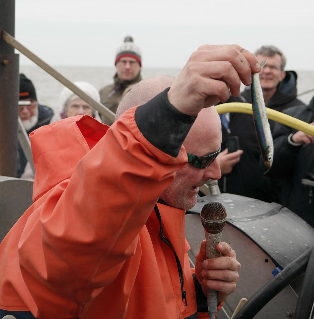 Frido geeft uitleg over de gevangen vis. Dit is een haring.