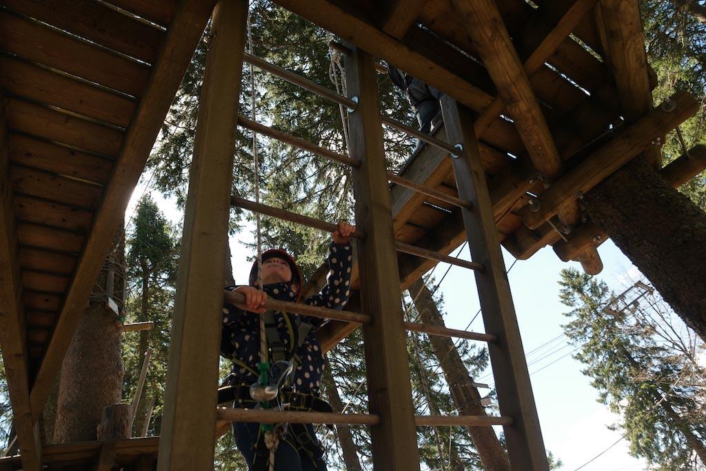 Maureen klimt, gezekerd, via de ladder omhoog.