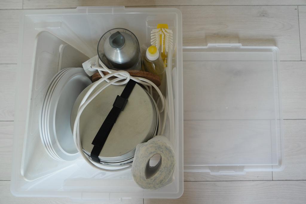 Het oude campingkookstelletje, borden, spiritusfles, afwasmiddel en afwasborstel, extra stekkerdoos.
