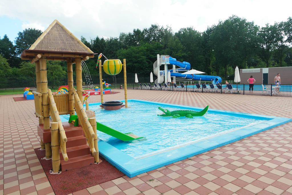 Het buitenzwembad met een badje voor de kleinste kinderen en erachter een zwembad met glijbaan voor de grote kinderen.