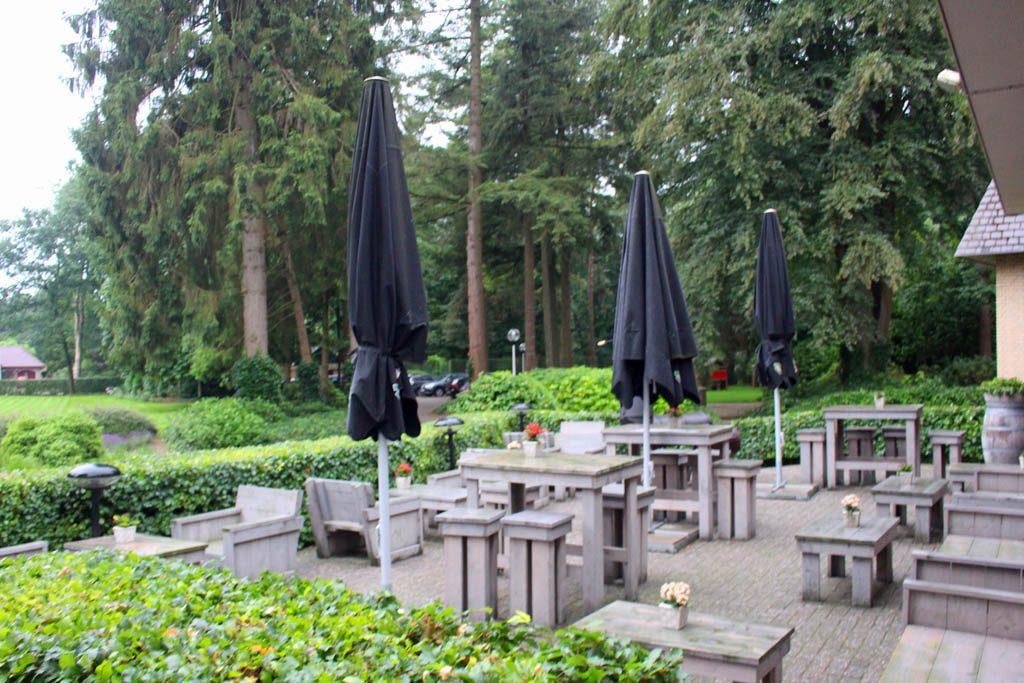 Buiten kun je heerlijk op het terras van de bosrijke omgeving genieten.