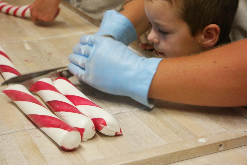Het doorknippen van de zuurstokken is te zwaar voor kinderen. Ze worden goed geholpen.