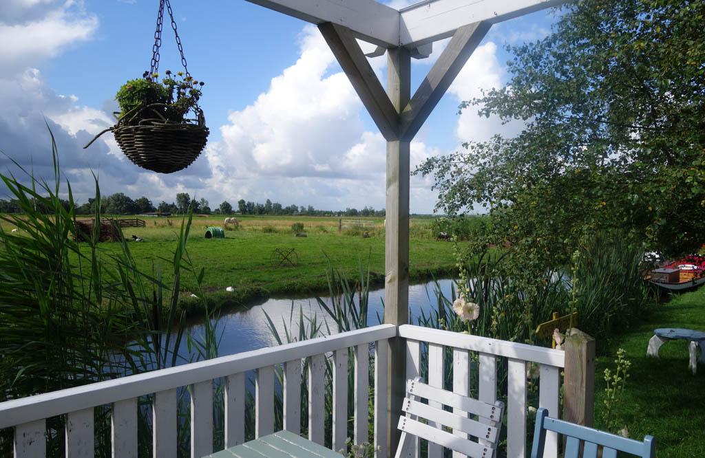 Vanaf het terras kijk je over het water en de weilanden.