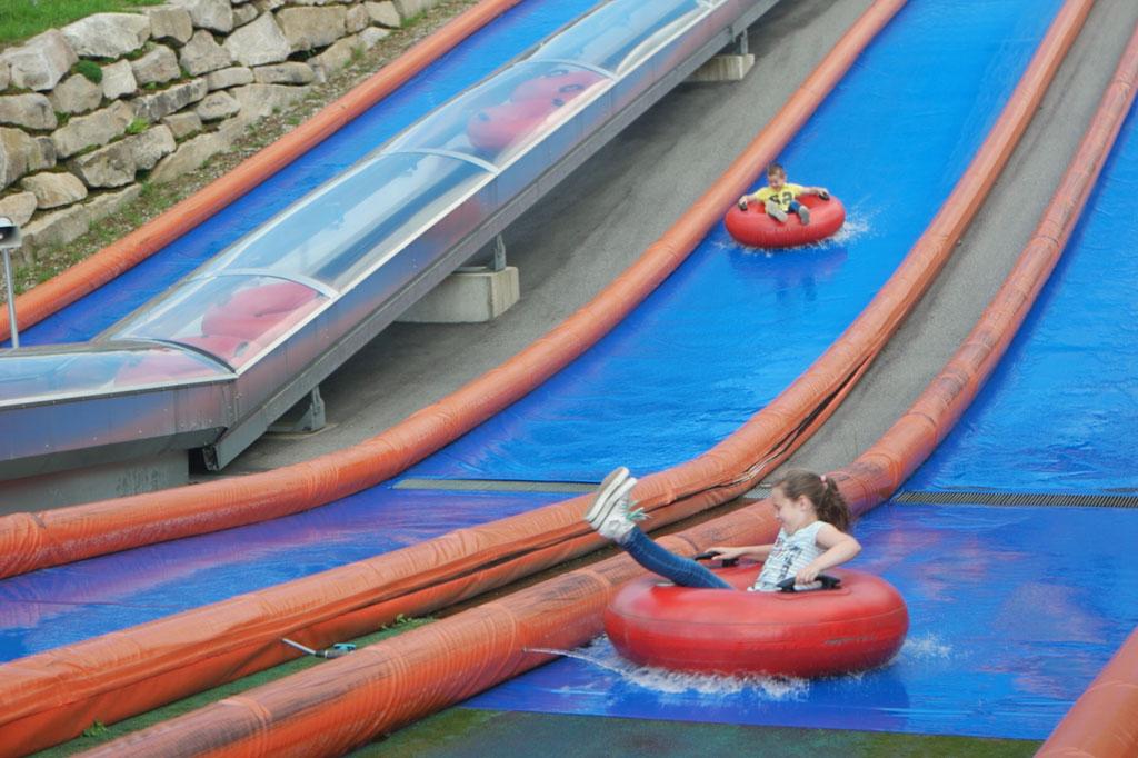 Met een grote zwemband de waterglijbaan af roetsjen.
