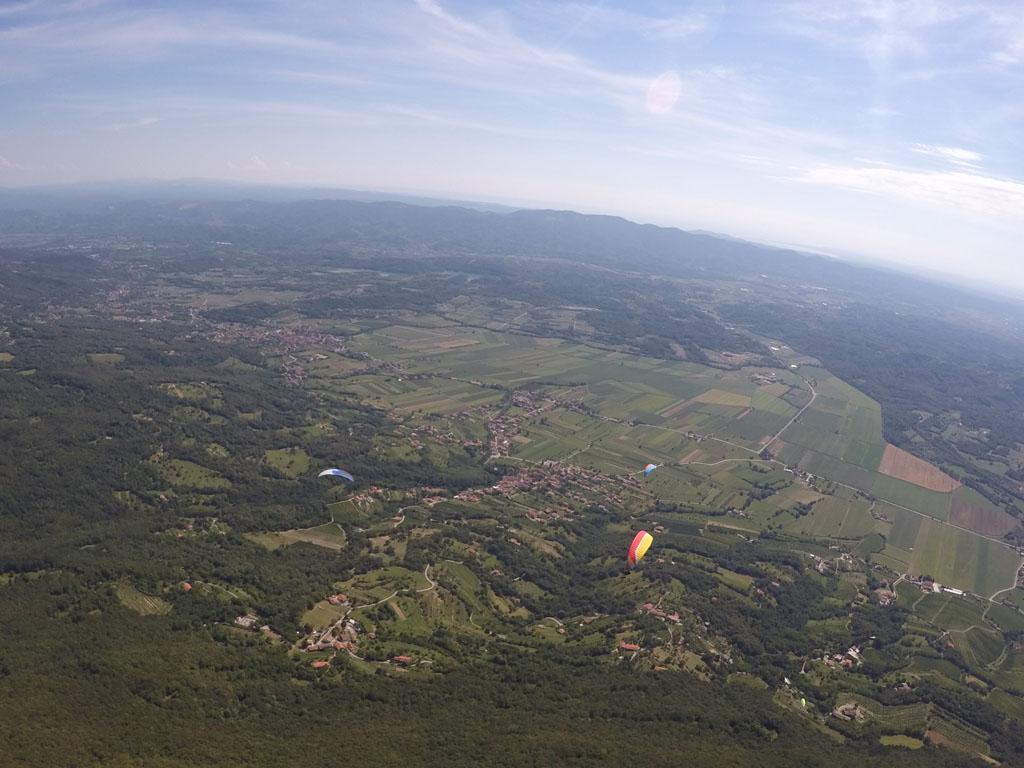 De kleurige schermen van de andere paragliders zien we boven, onder of naast ons voorbij komen.