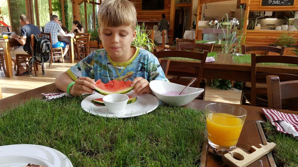 Ontbijten op het grasmatje op tafel en een beek naast de tafel.