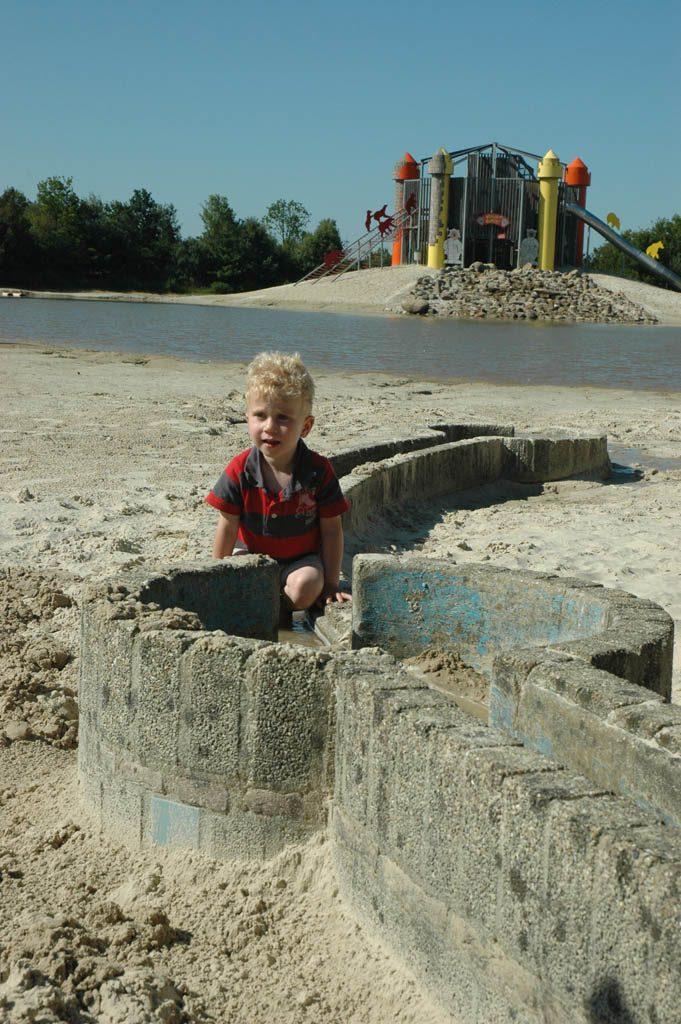 Spelen met een waterbaan op het strand bij de zwemvijver.