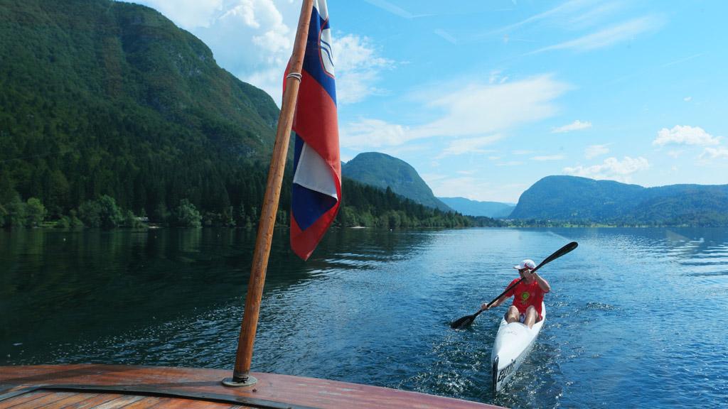 Een kanoer vaart op de golven van onze boot mee.